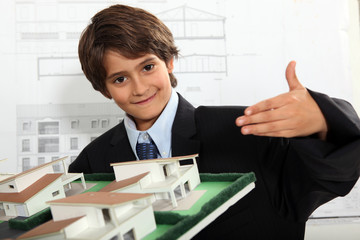Boy dressed as a businessman in an architect's office