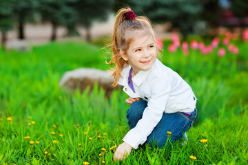 Sweet beautiful girl sitting on a green meadow with dandelions