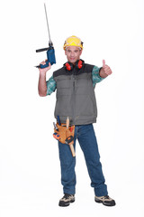A handyman with a drill giving the thumb up.
