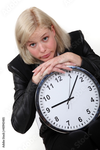 Blond businesswoman leaning on large clock