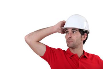Construction worker adjusting his hard hat