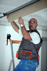 Manual worker repairing ceiling panel