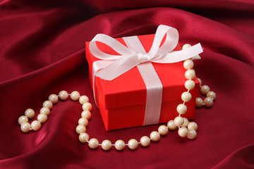 gift on red silk satin background.