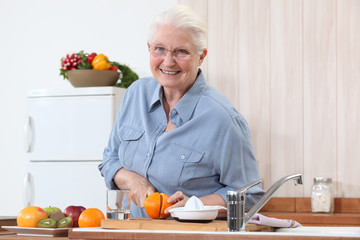 Elderly lady cutting an orange