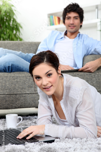 Woman laying on rug with laptop