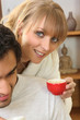 Woman drinking coffee next to husband