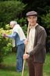 Senior couple raking leaves in the garden