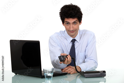businessman working on laptop holding out phone
