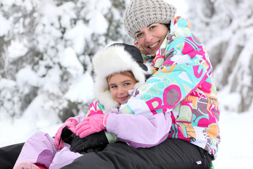 Mother and daughter playing in the snow together