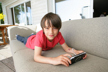 Little boy laying on sofa with hand-held video game