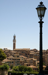 Lamppost and view of Torre del Mangia in Sienna