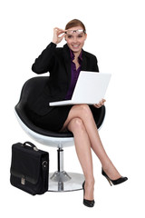 A businesswoman sitting in a modern chair.