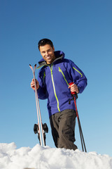 Middle Aged Man On Ski Holiday In Mountains