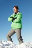 Man Standing In Snow Wearing Warm Clothes On Ski Holiday In Moun