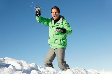 Man About To Throw Snowball Wearing Warm Clothes On Ski Holiday