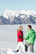 Couple Admiring Mountain View Whilst On Ski Holiday In Mountains