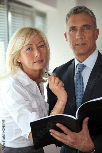 businessman and mature secretary consulting agenda