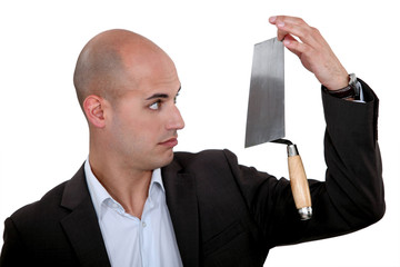 Businessman looking disbelievingly at a trowel