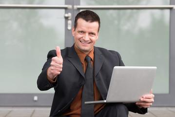 manager mit laptop zeigt daumen hoch