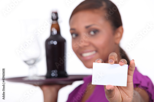 Waitress carrying tray and holding business card