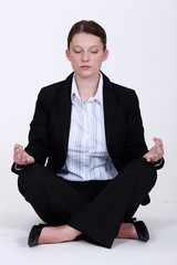 Young businesswoman meditating to relieve stress
