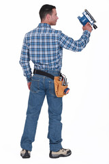 Rear view of a man with a sander