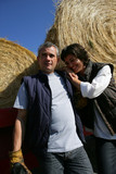 A farmer and his wife in front of bales of hay