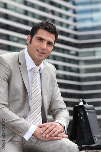 Young man relaxed sitting on a bench