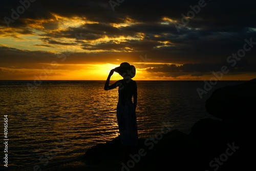 silhouette féminine devant le soleil couchant