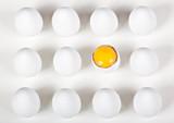 One broke egg amongst whole white eggs poster