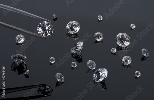 diamond in the tweezers on a background with other diamonds