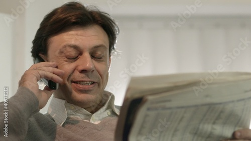 Happy businessman reading stock exchange listings on newspaper