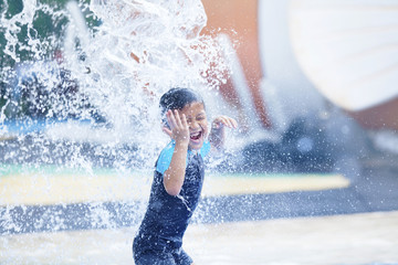 Cute asian boy playing at waterpark