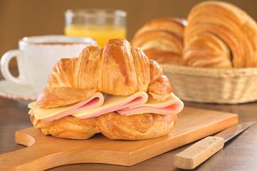 Croissant mit Schinken und Käse mit Kaffee und Orangensaft