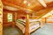 Log cabin bedroom under wood large ceiling.