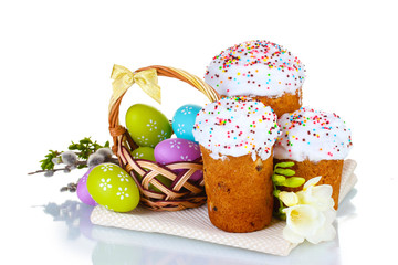 Beautiful Easter cakes, colorful eggs in basket and flowers