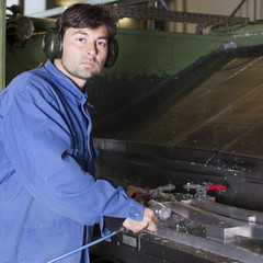 Metalworker cleaning a machine in fabric