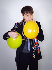 serious man in a business suit inflates balloons, party