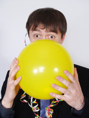 Young business man blowing up a yellow balloon