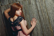 Beautiful sensual red-haired girl standing near a wooden wall