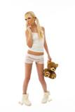 Beautiful blonde girl wearing pajamas holding a teddy bear