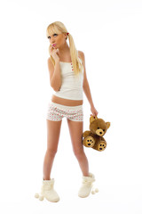 Beautiful blonde girl wearing pajamas holding a teddy bear