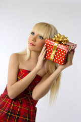 Pretty young blonde girl holding christmas gift in red dress