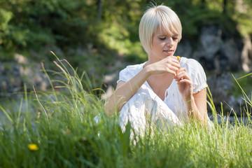 Frau spielt mit Blume