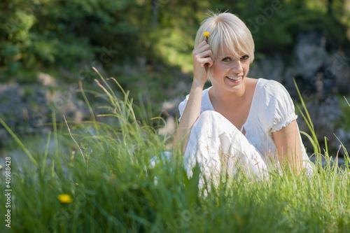 Frau sitzt in der Wiese