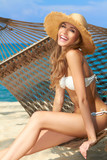 Fototapety Vivacious happy woman in bikini on hammock