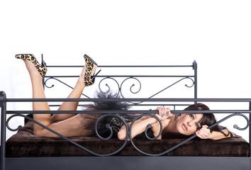 Hübsche Frau in sexy Unterwäsche im Bett blickt durch