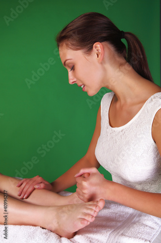 Pretty physiotherapist or reflexologist with patient