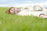 A happy woman laying on grass