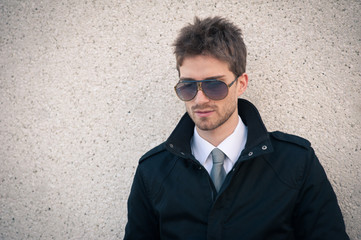 Young elegant man portrait with sunglasses against a wall.